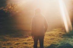 Homme marchant au mode de vie de voyage de forêt de lumière de coucher du soleil photo stock