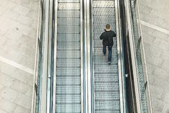 Homme marchant autour de regarder son téléphone portable Homme montant l'escalator photo libre de droits