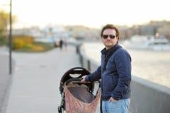 Homme marchant avec la poussette de bébé Photographie stock libre de droits