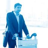 Homme marchant avec le chariot à aéroport Photo stock