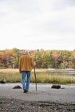 Homme marchant avec un bâton Photographie stock
