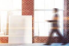 Homme marchant dans la chambre de brique avec l'affiche image stock