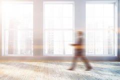 Homme marchant dans la chambre grise avec des fenêtres images stock