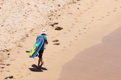 Homme marchant le long de la plage avec des Corps-conseils au-dessus d'épaule image stock