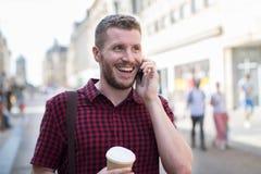 Homme marchant le long de la rue de ville parlant au téléphone portable photo libre de droits
