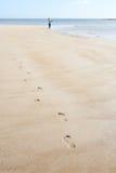 Homme marchant le long du rivage de la pêche de plage Images stock