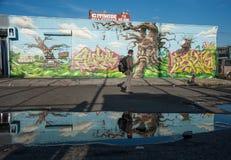 Homme marchant par des bâtiments du graffiti 5Pointz Images stock