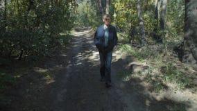 Homme marchant par la forêt en Sunny Weather banque de vidéos