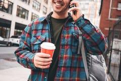 Homme marchant par la grande rue de ville avec la tasse de café chaud et à l'aide du smartphone pour appeler images libres de droits