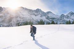 Homme marchant par la neige en montagnes Images stock