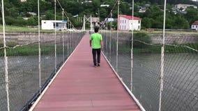 Homme marchant par le pont dans le concept de voyage de georigia de borjomi banque de vidéos