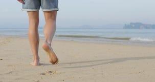 Homme marchant pour arroser sur la plage, vue arrière de jambes de dos masculin de plan rapproché banque de vidéos