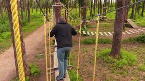 Homme marchant sur des câbles entre les arbres banque de vidéos