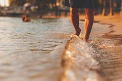 Homme marchant sur l'écoulement d'eau de plage et de mer dans le temps de coucher du soleil images libres de droits