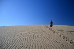 Homme marchant sur la dune Image stock