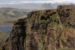 Homme marchant sur la grande falaise de l'Islande dans le paysage dramatique photos stock