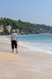 Homme marchant sur la plage Photographie stock libre de droits