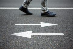 Homme marchant sur la route avec des flèches Images libres de droits