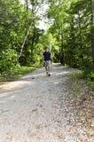 Homme marchant sur le journal de forêt Photographie stock
