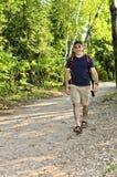Homme marchant sur le journal de forêt Photos libres de droits