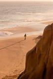 Homme marchant sur seule la plage Photos stock