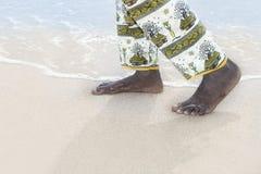 Homme marchant sur une plage blanche de sable Images stock