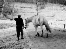 Homme marchant un cheval dans le village Photos libres de droits