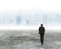 Homme marchant vers des bâtiments de ville en brume photos stock