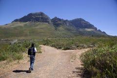 Homme marchant vers le haut d'une montagne Image libre de droits