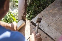 Homme martelant un clou dans le plancher image stock