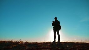 Homme masculin en valeur lui de touristes avec la lumière du soleil de navigation de smartphone de sac à dos avec des supports de clips vidéos