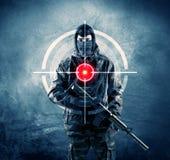 Homme masqué de terroriste avec la cible d'arme à feu et de laser sur son corps photographie stock