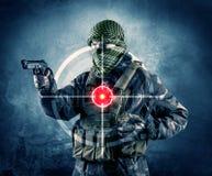 Homme masqué de terroriste avec la cible d'arme à feu et de laser sur son corps photographie stock libre de droits