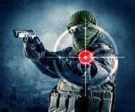 Homme masqué de terroriste avec la cible d'arme à feu et de laser sur son corps image stock