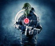 Homme masqué de terroriste avec la cible d'arme à feu et de laser sur son corps image libre de droits
