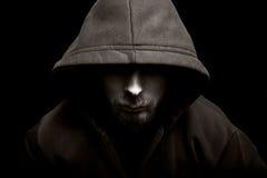 Homme mauvais effrayant avec le capot dans l'obscurité Image libre de droits
