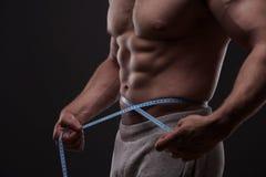 Homme mesurant sa taille avec un ruban métrique Photo libre de droits