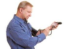 Homme mesurant sa tension artérielle photos stock