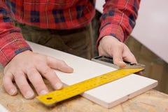 Homme mesurant un panneau Photo libre de droits