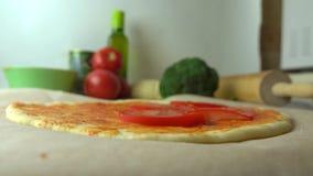 Homme mettant des tranches de tomate au-dessus de base de pizza Cuisson, une partie de l'ensemble fin 4K vers le haut de tir banque de vidéos