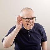 Homme mettant en forme de tasse son oreille Images stock