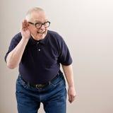 Homme mettant en forme de tasse son oreille Photographie stock libre de droits