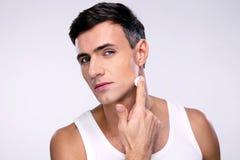 Homme mettant la crème sur un visage Photos stock