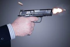 Homme mettant le feu à une arme à feu Image stock