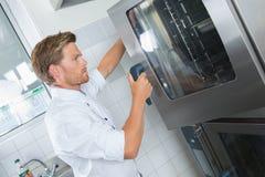 Homme mettant le plateau dans le four dans la cuisine photos stock