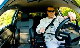 Homme mettant sa ceinture de sécurité en fonction Photographie stock