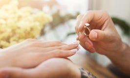 Homme mettant sur la bague de fiançailles de doigt de fille Photographie stock libre de droits