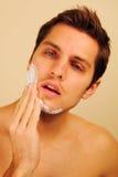 Homme mettant sur la crème à raser Photographie stock
