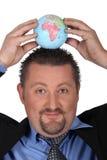 Homme mettant un globe sur la tête Image libre de droits