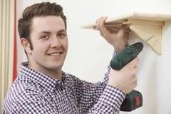 Homme mettant vers le haut de l'étagère en bois à la maison utilisant le foret électrique Image stock